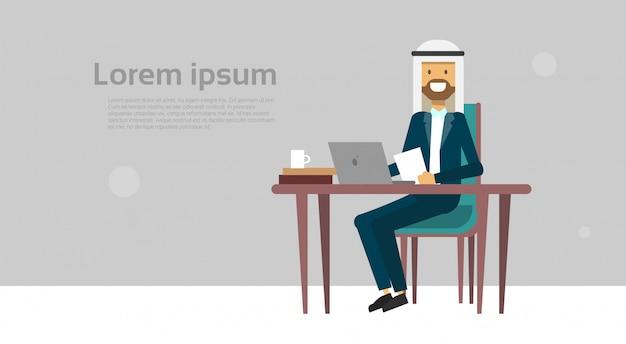 Uomo d'affari arabo che si siede al concetto della rottura del cofee dell'uomo di affari del computer portatile della tenuta della scrivania