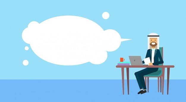 Uomo d'affari arabo che si siede al concetto della rottura del cofee dell'uomo di affari delle bolle del computer portatile della tenuta della scrivania