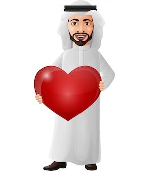 Uomo d'affari arabo del fumetto che tiene un cuore rosso