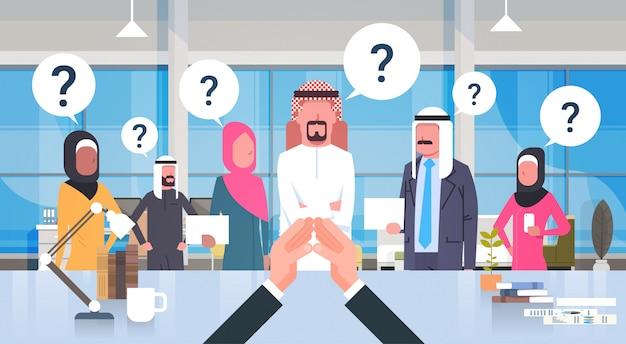 Uomo d'affari capo guardando business brainstorming squadra di persone arabe con theseion mark seduto alla scrivania, capo con gruppo di businesspeople saudite in ufficio moderno