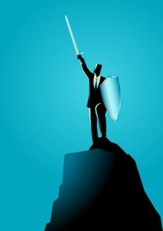 Uomo d'affari che alza una spada e uno scudo sopra roccia