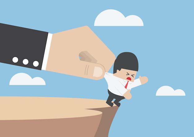 Uomo d'affari che cadendo dalla scogliera viene aiutato da una grossa mano