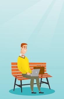 Uomo d'affari che lavora al computer portatile all'aperto.