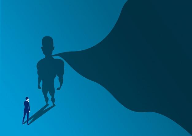 Uomo d'affari che osserva come successo con un supereroe con ombra del capo sulla parete. ambizione e concetto di successo aziendale. potere dell'eroe di leadership, motivazione e simbolo di forza interiore.