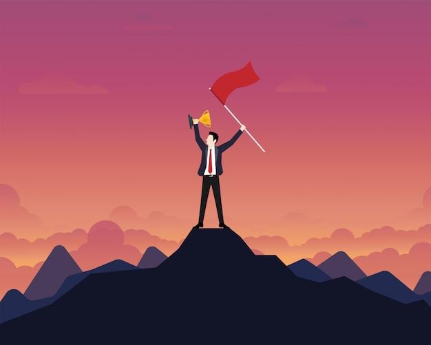 Uomo d'affari che ostacola una tazza del trofeo dell'oro con la bandiera di successo sopra la montagna