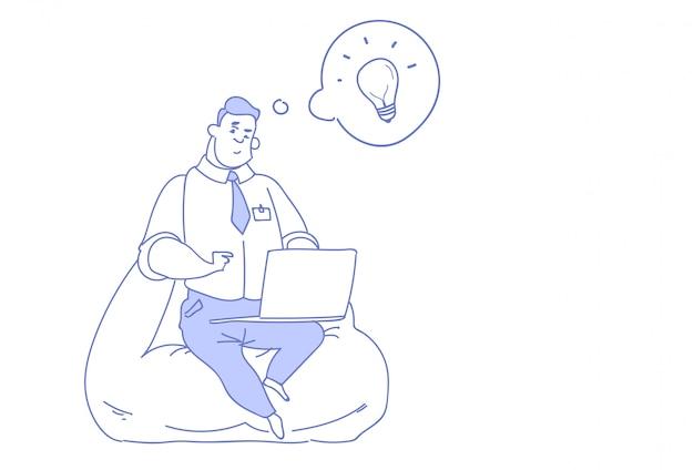 Uomo d'affari che per mezzo del computer portatile che genera innovazione di idee creative