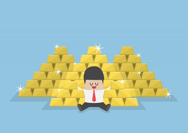 Uomo d'affari che si siede con un mucchio delle barre di oro