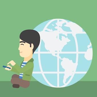 Uomo d'affari che si siede vicino al globo della terra.