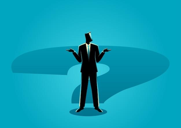 Uomo d'affari che sta sull'ombra del punto interrogativo