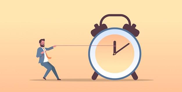 Uomo d'affari che tira orologio freccia termine di gestione del tempo concetto uomo d'affari in tuta spingendo indietro lancetta delle ore carattere maschile piatto orizzontale a figura intera