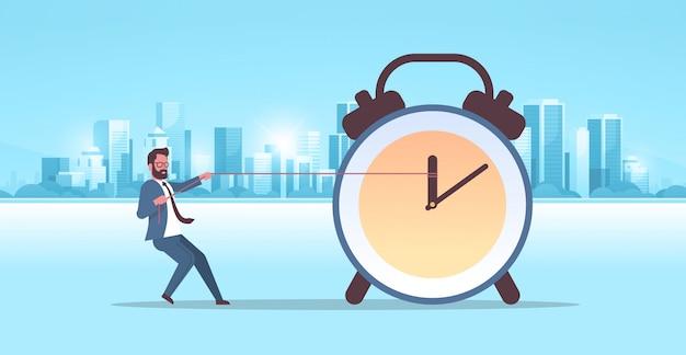 Uomo d'affari che tira orologio freccia termine di gestione del tempo concetto uomo d'affari in tuta spingendo indietro lancetta delle ore moderna città costruzioni città paesaggio urbano sfondo orizzontale piena lunghezza