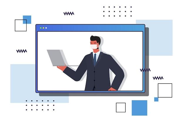 Uomo d & # 39; affari che utilizza la maschera da portare del laptop per prevenire la pandemia di coronavirus