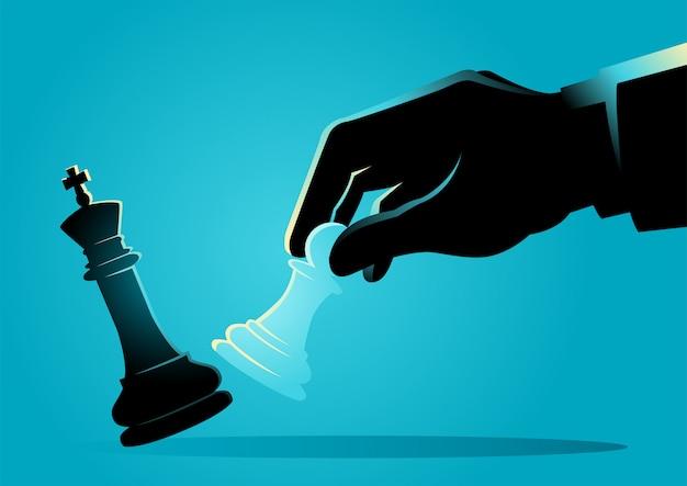 Uomo d'affari che utilizza un pegno per dare dei calci ad un re nella partita a scacchi