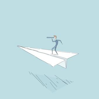 Uomo d'affari che vola sull'aereo di carta che osserva con il binocolo sul riuscito concetto futuro di sviluppo della crescita