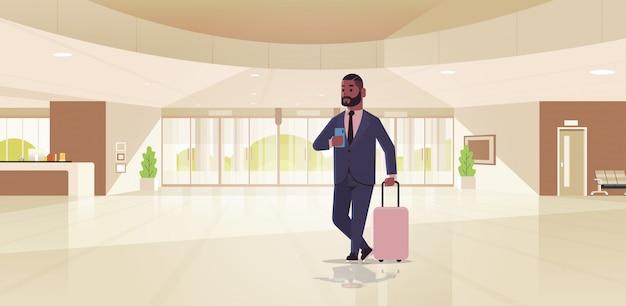 Uomo d'affari con bagagli moderno reception area business uomo afroamericano azienda ragazzo valigia in piedi nella hall contemporanea hall dell'hotel interno