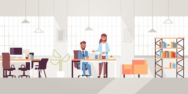 Uomo d'affari con l'assistente femminile che per mezzo del computer portatile che discute nuovo progetto nel corso della riunione sul posto di lavoro interno di lavoro creativo ufficio moderno interno