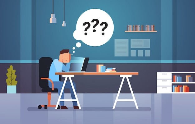 Uomo d'affari confuso usando il portatile sul posto di lavoro pensando a risposte
