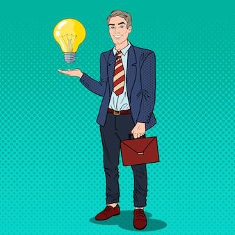 Uomo d'affari di pop art con la lampadina di idea creativa