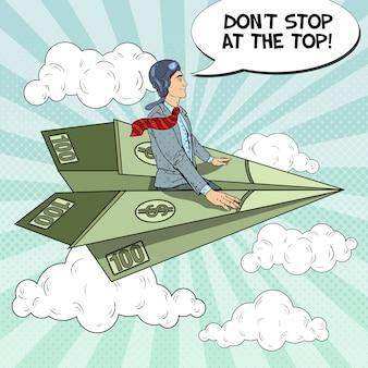 Uomo d'affari di successo di pop art volando sull'aereo di carta del dollaro.