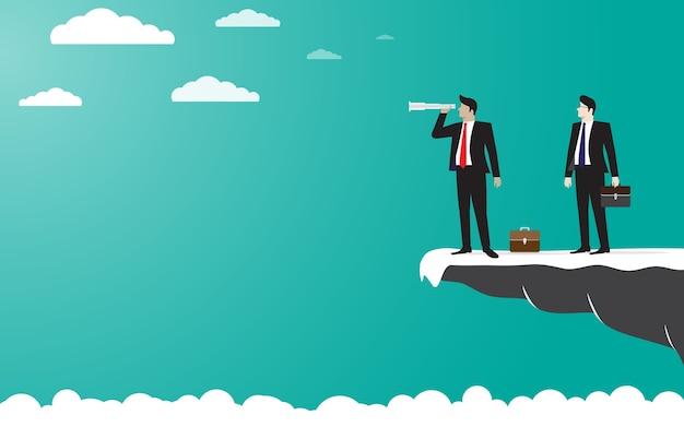 Uomo d'affari due che sta sopra la scogliera della montagna facendo uso del binocolo che cerca successo