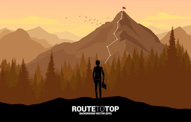 Uomo d'affari e rotta verso la cima della montagna