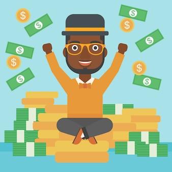 Uomo d'affari felice che si siede sulle monete.
