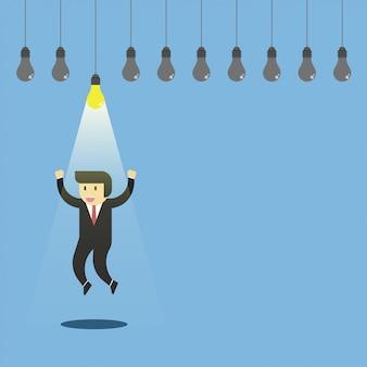 Uomo d'affari felice saltando sotto la lampada splendente.
