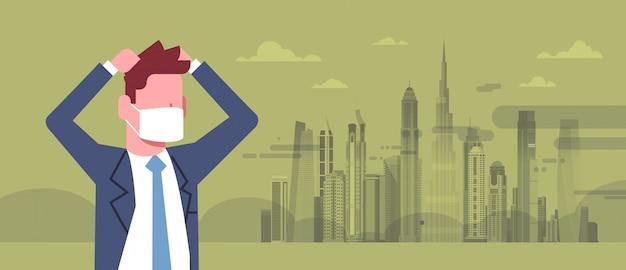 Uomo d'affari in maschera tenendo la testa con la città inquinata