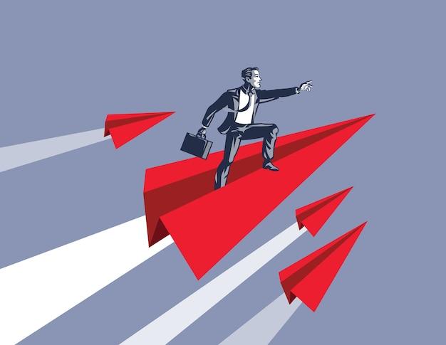 Uomo d'affari in piedi sul razzo aeroplano di carta come simbolo di fiducia per affrontare il successo e il futuro d'oro