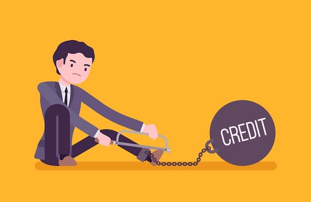 Uomo d'affari incatenato con un credito di peso metallico, segando