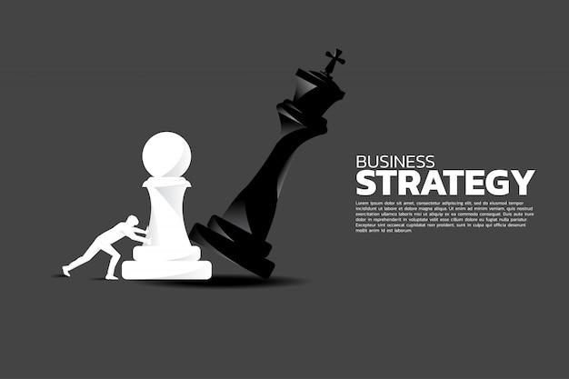 Uomo d'affari spingere pezzo di scacchi pegno a scacco matto il re.