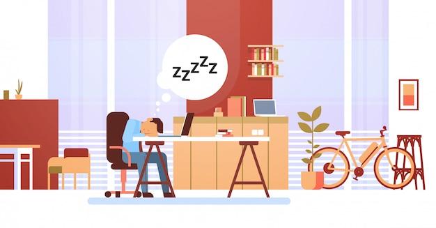 Uomo d'affari stanco che dorme sul posto di lavoro