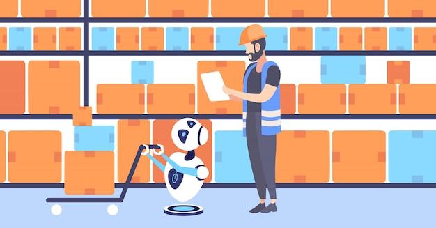 Uomo dei magazzinieri in uniforme con il robot sveglio del corriere che tira le scatole di cartone sull'orizzontale moderno dell'interno di stoccaggio di concetto di intelligenza artificiale del carrello a mano del carrello