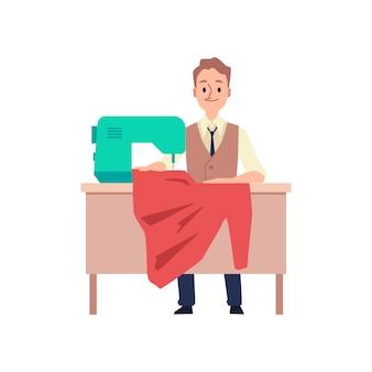 Uomo del sarto che si siede dietro la tavola con la macchina per cucire che tiene panno rosso