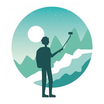 Uomo del viaggiatore che cattura selfie nel paesaggio