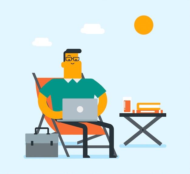 Uomo di affari che lavora ad un computer portatile sulla spiaggia.
