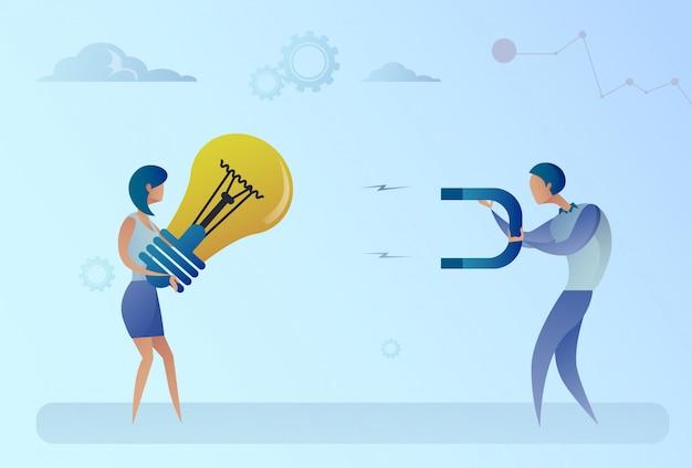Uomo di affari che ruba idea della lampadina dal concetto del magnete della tenuta della donna