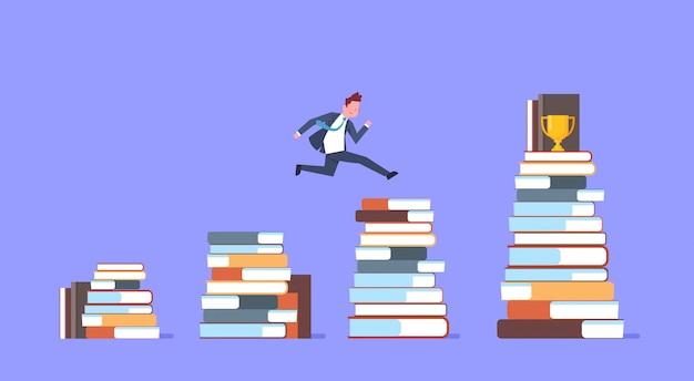 Uomo di affari che salta sopra le pile di libri alla tazza dorata vincitore dell'uomo d'affari riuscito
