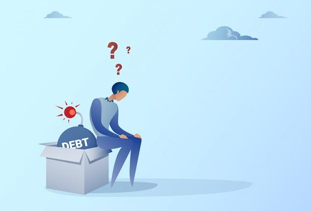 Uomo di affari che si siede sul concetto di crisi di finanza di debito di credito della bomba