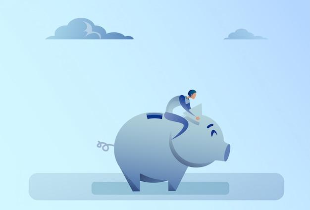 Uomo di affari che si siede sul concetto di risparmio dei soldi del porcellino salvadanaio