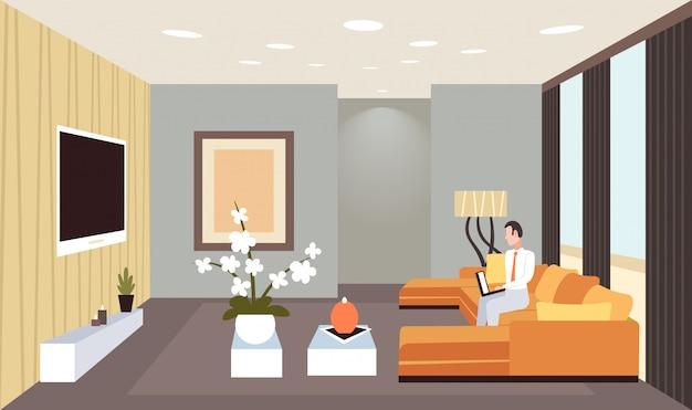 Uomo di affari che si siede sullo strato facendo uso orizzontale orizzontale moderno domestico interno interno del salone contemporaneo del computer portatile