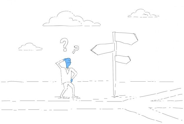 Uomo di affari sullo sguardo della strada trasversale al bordo del segno che sceglie concetto di direzione