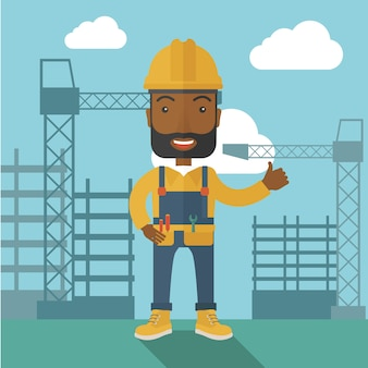 Uomo di colore che sta davanti alla torre della gru di costruzione.