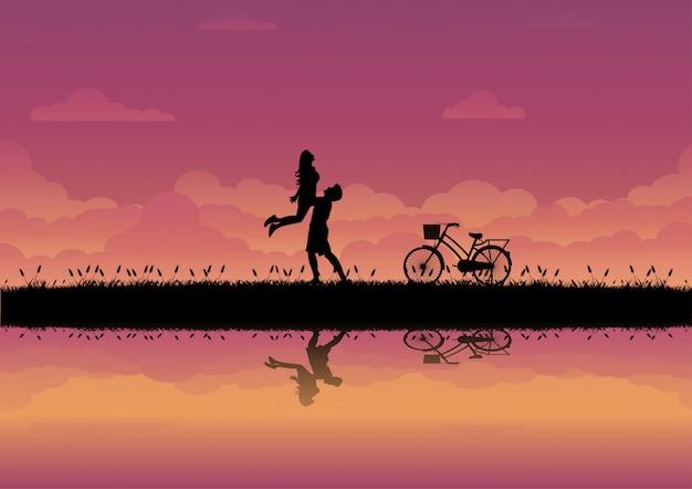 Uomo e donna che giocano felicemente sul prato con il fondo di tramonto