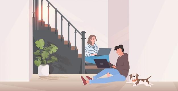 Uomo e donna che utilizza computer portatili, coppia seduta sulla scala trascorrere del tempo insieme, interno corridoio moderno