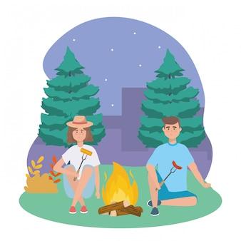 Uomo e donna con fuoco di legna e salsiccia con pannocchia