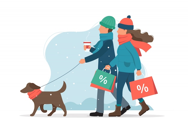 Uomo e donna con i sacchetti di vendita, a spasso il cane in inverno.