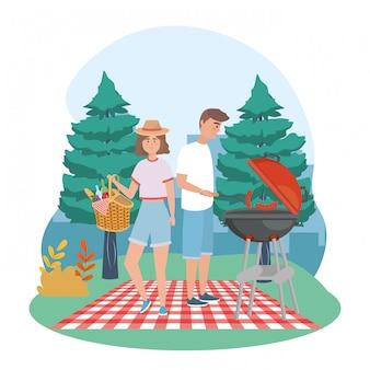 Uomo e donna con salsicce alla griglia e cesto con cibo