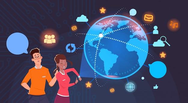 Uomo e donna sul globo del mondo con le icone di social media background internet e tecnologia moderna