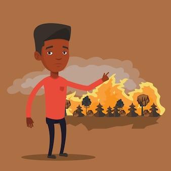 Uomo in piedi sullo sfondo di un incendio.